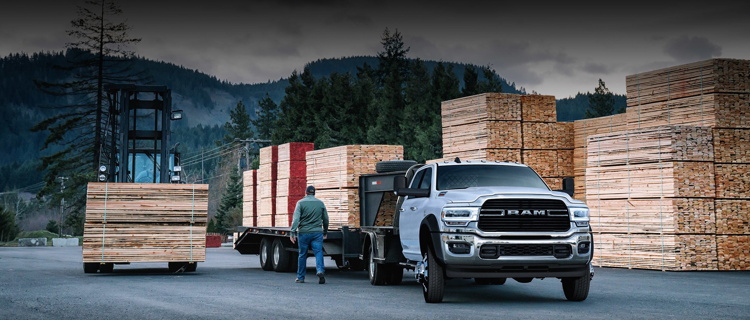 The white 2020 Ram Chassis Cab is parked in a loading zone while towing lumbers