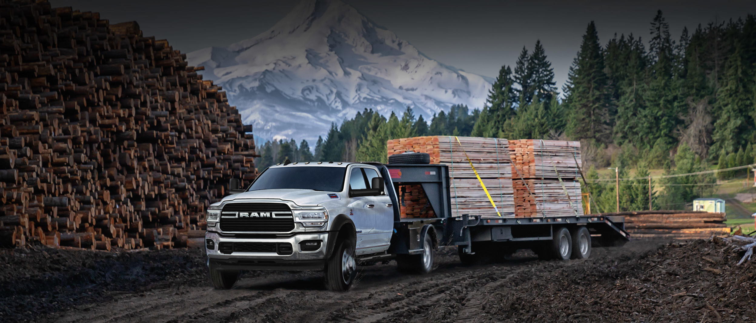 The white 2020 Ram Chassis Cab towing lumbers in construction site