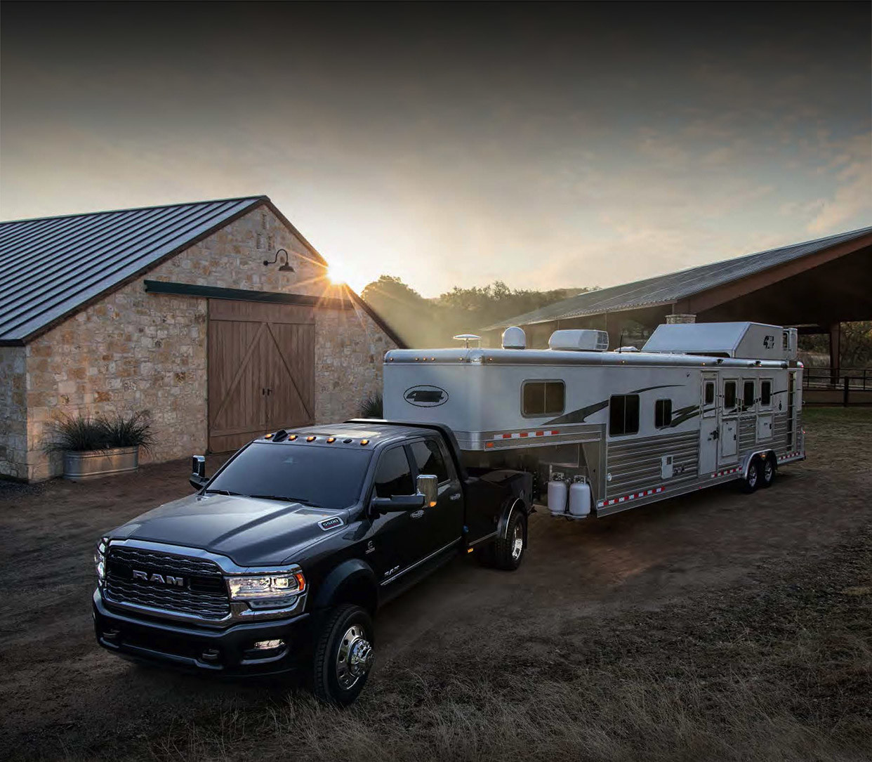 The black 2020 Ram Chassis Cab connected with camp trailer parked in front of barnyard