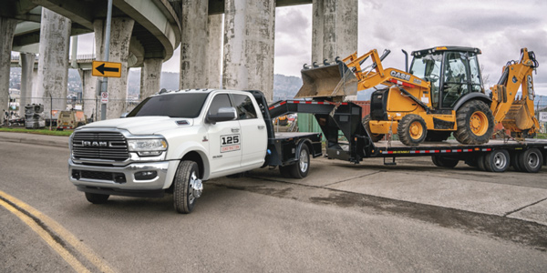2020 Ram Chassis Cab towing an excavator from a construction site