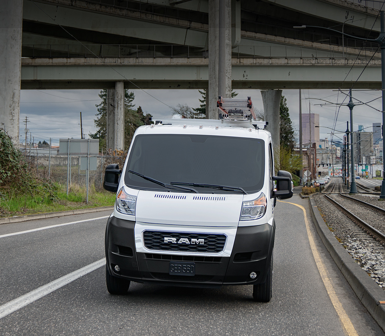 Front view of the white 2019 Ram ProMaster driving down a road beside train tracks