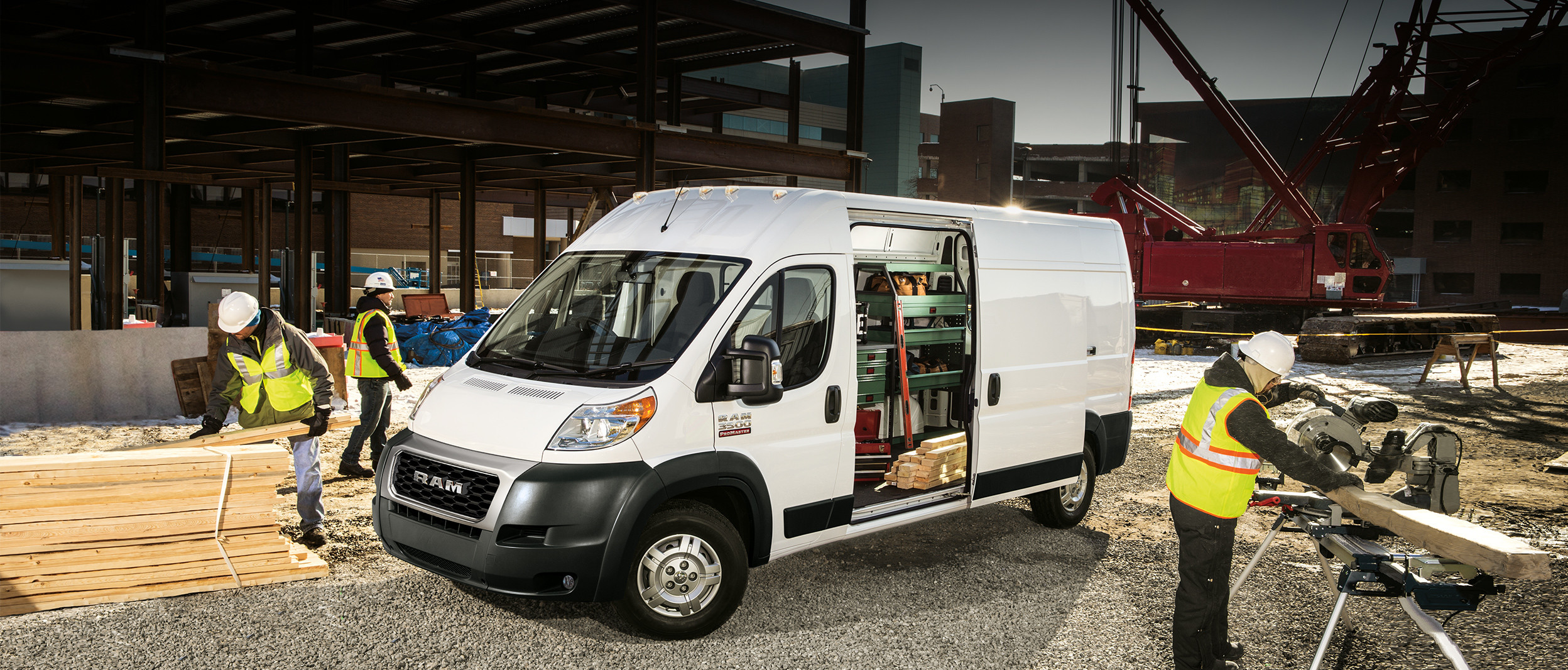 White 2019 Ram ProMaster, parked in a construction zone with 3 workers around the vehicle.