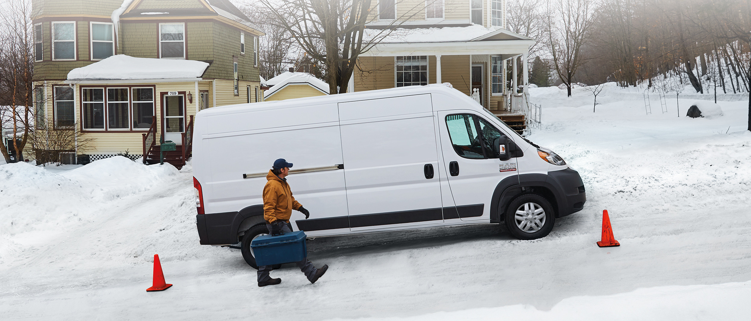 Side view of the white 2020 Ram ProMaster parked on the side of the road while a service person walks beside it
