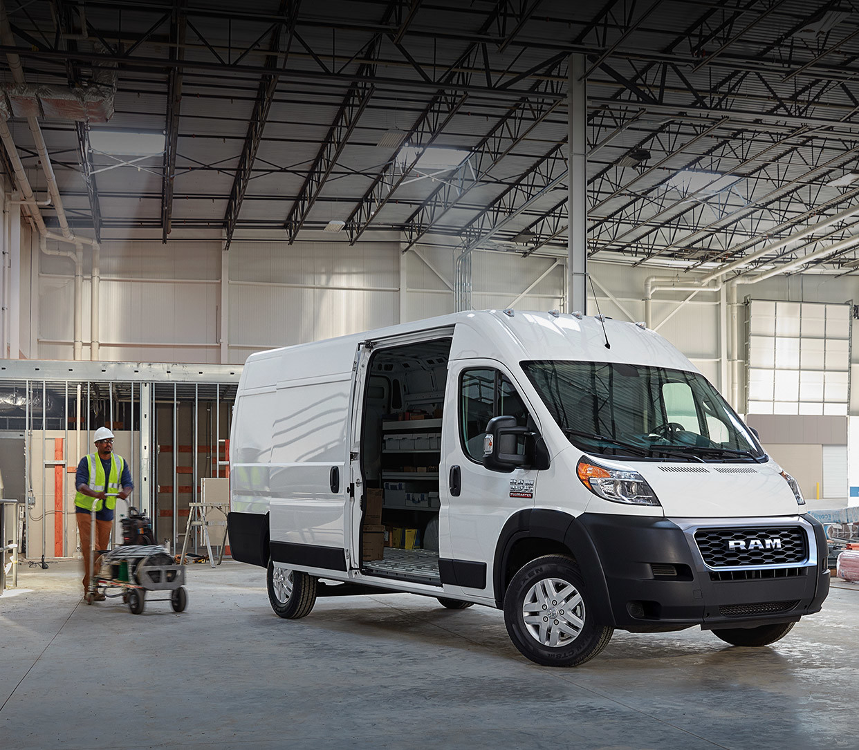 The white 2020 Ram ProMaster parked inside a cargo while man walking to its side door