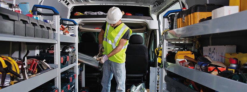 A worker cutting an aluminum sheet in the 2020 Ram ProMaster loaded with construction tools on the side walls