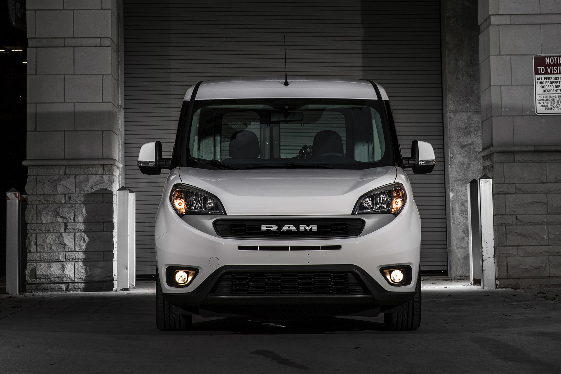 Front view of 2020 Ram ProMaster City parked in front of garage door in an urban area